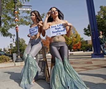 Topless PETA mermaids protest fish murder