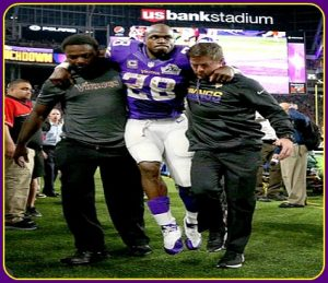 Adrian Peterson being assisted off the field since new home field forgot to buy a golf cart.